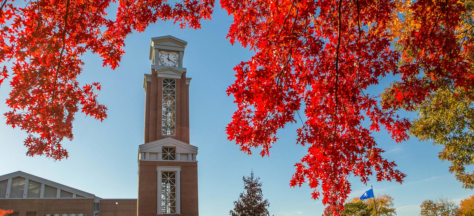 View of the Eastern clocktower with red fall foliage in the foreground