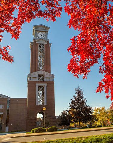 Photo of the Eastern clock tower surrounded by fall foliage