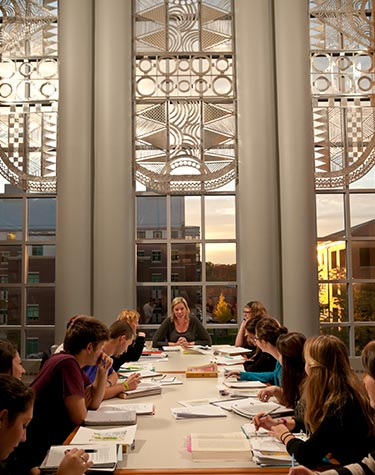 Professor teaching with the library windows as a backdrop