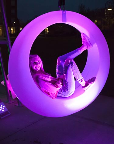 Student sitting inside a circular hanging glow-in-the-dark object