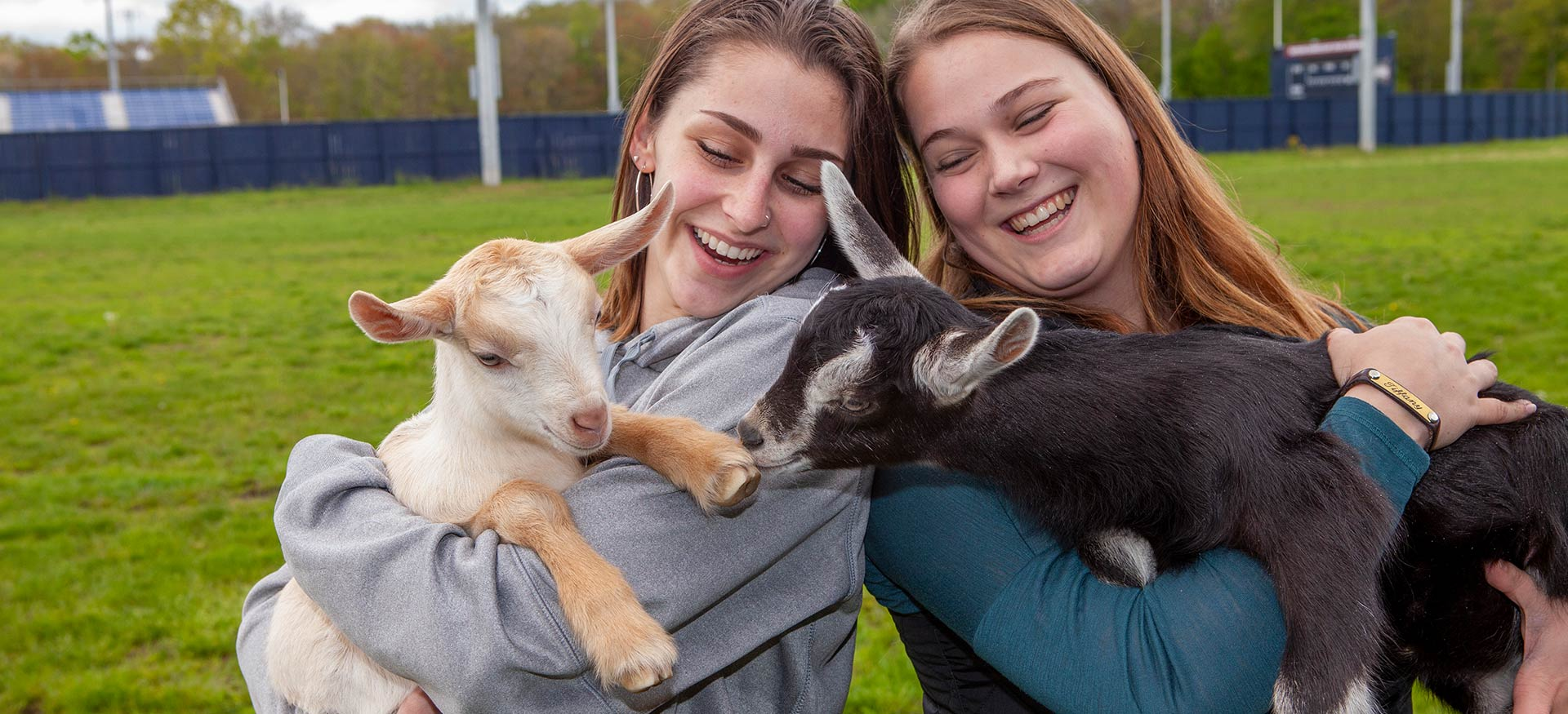 Students holding baby goats