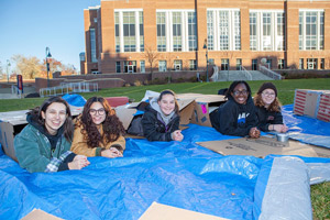 Student's who volunteered to sleep in the cold pose for a photo.